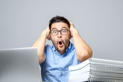 Portrait of amazed man with laptop computer. Over gray background Stock Image