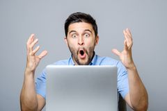 Portrait of amazed man with laptop computer. Over gray background Royalty Free Stock Photo