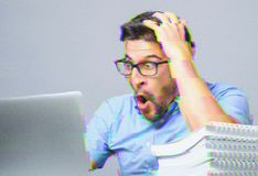 Portrait of amazed man with laptop computer. Digital glitch effect added Stock Image