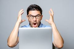 Portrait of amazed man with laptop computer. Over gray background Royalty Free Stock Photos