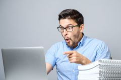 Portrait of amazed man with laptop computer. Over gray background Stock Photo