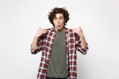 Portrait of amazed nervous shocked young man in casual clothes standing, looking camera isolated on white wall stock images