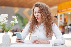 Portrait of amazed woman looks with surprised expression in smart phone, doesn`t expect to recieve message from male, sits at tabl. E in cafe, decorated with Stock Photography