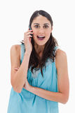 Portrait of an amazed woman making a phone call Stock Image
