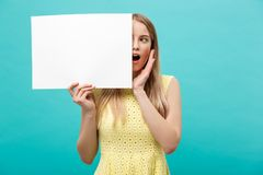 Portrait of amazed young blond woman holding blank sign with copy space on blue studio background. Showing shocked. Surprise face Stock Images