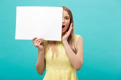 Portrait of amazed young blond woman holding blank sign with copy space on blue studio background. Showing shocked. Surprise face Royalty Free Stock Photography