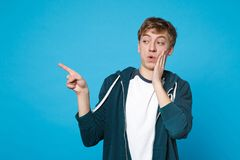 Portrait of amazed young man in casual clothes pointing index fingers aside putting hand on cheek isolated on blue. Background in studio. People sincere royalty free stock photos