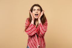 Portrait of amazed young woman in casual clothes keeping mouth wide open putting hands on face isolated on pastel beige royalty free stock photography
