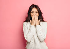 Portrait of amazed young woman over pink background. Shocked brunette girl in casual white sweater covering mouth isolated over color wall Royalty Free Stock Photo