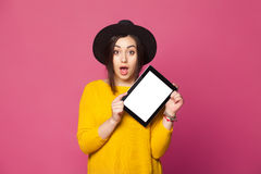 Portrait of amazed young woman showing tablet screen. Portrait of amazed young woman showing tablet computer screen isolated on a pink background Royalty Free Stock Photo
