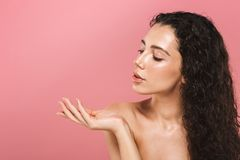 Beautiful young woman with healthy skin posing isolated over pink background looking aside. royalty free stock photo