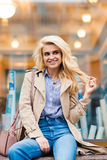 Portrait of an amazing happy blonde model posing while sitting on a shop sill in a warm autumn day, Royalty Free Stock Photography
