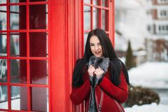Portrait amazing smiled winter young woman walking on street full with snow Red telephone box, british style Stock Image