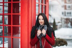 Portrait amazing smiled winter young woman walking on street full with snow Red telephone box, british style Stock Photography