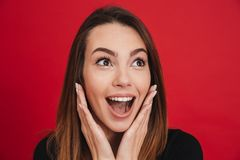 Portrait of amazing woman 20s raising arms to face and expressin. G surprise isolated over red background Royalty Free Stock Photo