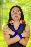 Portrait amazonian exotic woman with facial paint and black dress, posing proudly for camera, arms crossed across upper Stock Images