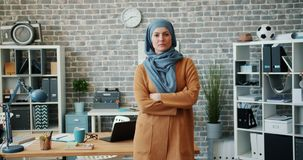 Portrait of ambitious mixed race woman in hijab standing in office arms crossed. Portrait of ambitious mixed race woman in hijab standing in office with arms stock video footage