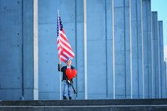 A portrait of american boy holding  flag of United States of America. A five years old happy boy is holding american flag and big red heart  on grey, industrial Stock Image