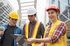 Portrait of American female engineer with team. Portrait of happy American female engineer smilling while other engineering men look at project plan stock photography
