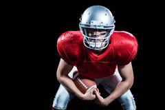 Portrait of American football player bending while holding ball Royalty Free Stock Images
