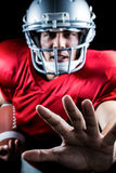 Portrait of American football player defending while holding ball. Over black background stock photo