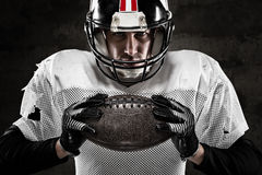 Portrait of american football player holding a ball. And looking at camera Royalty Free Stock Image