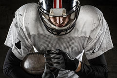 Portrait of american football player holding a ball. And looking down Royalty Free Stock Image