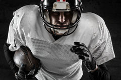 Portrait of american football player holding a ball. And running Royalty Free Stock Photo