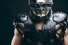 Portrait of american football player in protective shields on naked torso