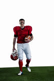 Portrait of american football player walking and holding football and helmet Royalty Free Stock Photography