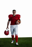 Portrait of american football player walking and holding football and helmet Royalty Free Stock Photos