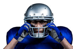 Portrait of American football player wearing helmet. Against white background Royalty Free Stock Images