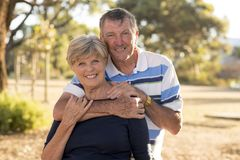 Portrait of American senior beautiful and happy mature couple around 70 years old showing love and affection smiling together in t. He park having a romantic Stock Photography