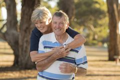 Portrait of American senior beautiful and happy mature couple around 70 years old showing love and affection smiling together in t. He park having a romantic Royalty Free Stock Photo