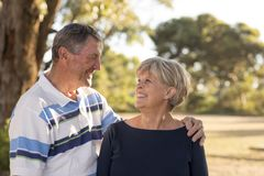 Portrait of American senior beautiful and happy mature couple around 70 years old showing love and affection smiling together in t. He park having a romantic Royalty Free Stock Image