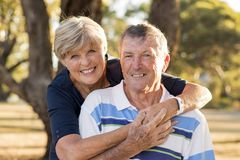 Portrait of American senior beautiful and happy mature couple around 70 years old showing love and affection smiling together in t. He park having a romantic Stock Images