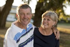 Portrait of American senior beautiful and happy mature couple around 70 years old showing love and affection smiling together in t. He park having a romantic Royalty Free Stock Images