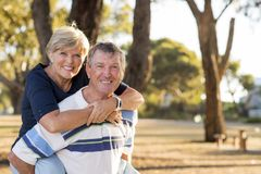 Portrait of American senior beautiful and happy mature couple around 70 years old showing love and affection smiling together in t. He park having a romantic stock photos