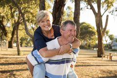 Portrait of American senior beautiful and happy mature couple around 70 years old showing love and affection smiling together in t. He park having a romantic Stock Image