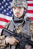 Portrait of American soldier. Portrait of armed American soldier over american flag in background stock photos
