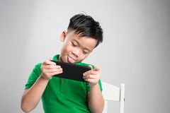 Portrait of an amused cute little kid playing games on smartphone isolated over gray background stock photography