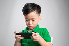 Portrait of an amused cute little kid playing games on smartphone isolated over gray background stock photos