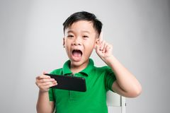 Portrait of an amused cute little kid playing games on smartphone isolated over gray background stock image