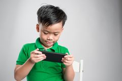Portrait of an amused cute little kid playing games on smartphone isolated over gray background royalty free stock photos