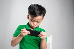 Portrait of an amused cute little kid playing games on smartphone isolated over gray background royalty free stock images