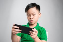 Portrait of an amused cute little kid playing games on smartphone isolated over gray background stock images