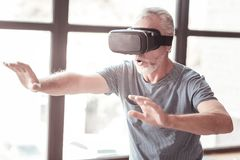 Portrait of amused elderly man wearing virtual glasses. Excitement. Portrait of amused bearded elderly man wearing virtual glasses while expressing cheer and stock photo