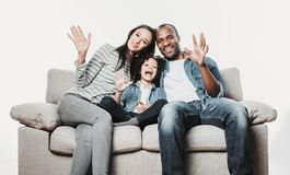 Satisfied family sitting on sofa and greeting. Portrait of amused parents and daughter taking seat on couch and waving with smile. Isolated on background royalty free stock photo