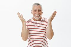 Portrait of amused and surprised happy senior father on pension standing delighted gesturing with rased palms and. Smiling being entertained and thrilled how stock photo
