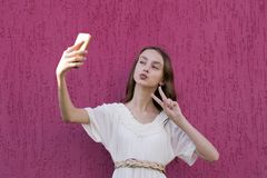 Cute happy teenager posing for picture. Portrait of amusing girl taking selfie on modern smartphone. Lovely young woman looking at display of cellphone with royalty free stock images